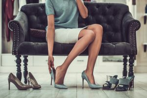 A businesswoman sitting on a sofa, putting on her shoes